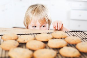 A child looking at freshly baked cookies, about to steal one