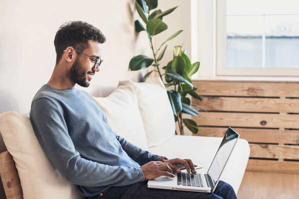 man with glasses sitting on couch with laptop computer