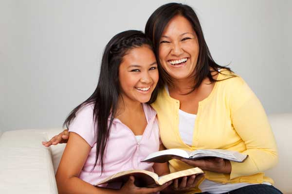 two women smiling for photo holding open books