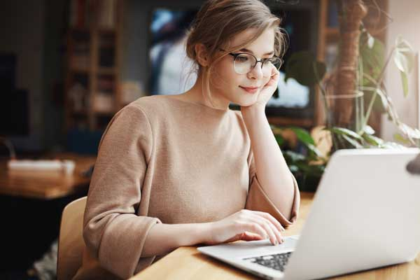 woman with glasses scrolls through document on laptop computer